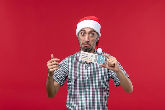 Vue de face jeune homme tenant un billet d'avion sur un bureau rouge