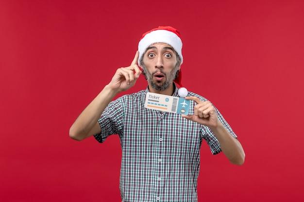 Vue de face jeune homme tenant un billet d'avion sur fond rouge