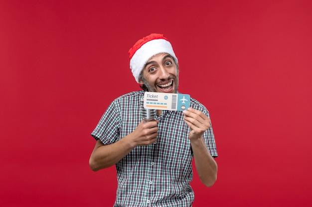 Vue de face jeune homme tenant billet d'avion et micro sur un bureau rouge