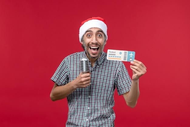 Vue de face jeune homme tenant billet d'avion et micro sur fond rouge