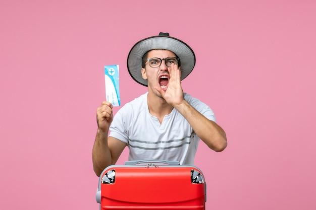 Vue de face d'un jeune homme tenant un billet d'avion pour des vacances criant sur un mur rose