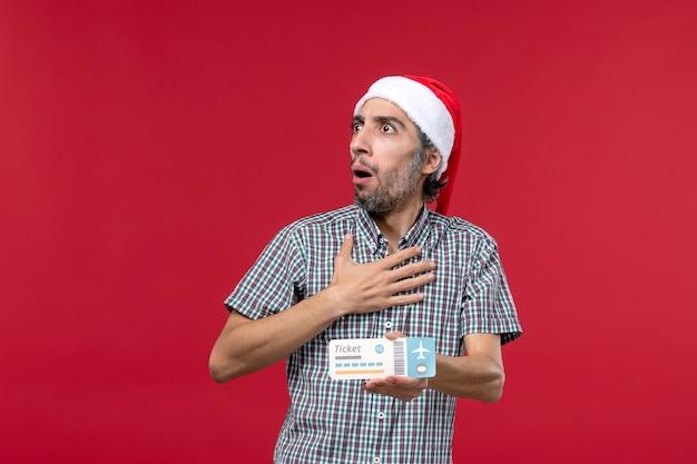 Vue de face jeune homme tenant un billet sur fond rouge