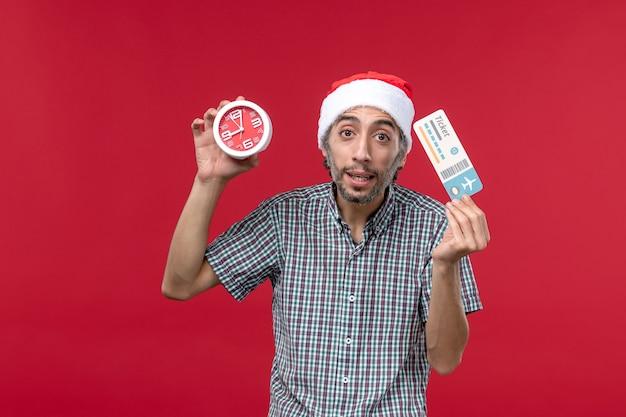 Vue de face jeune homme tenant billet et horloge sur un bureau rouge