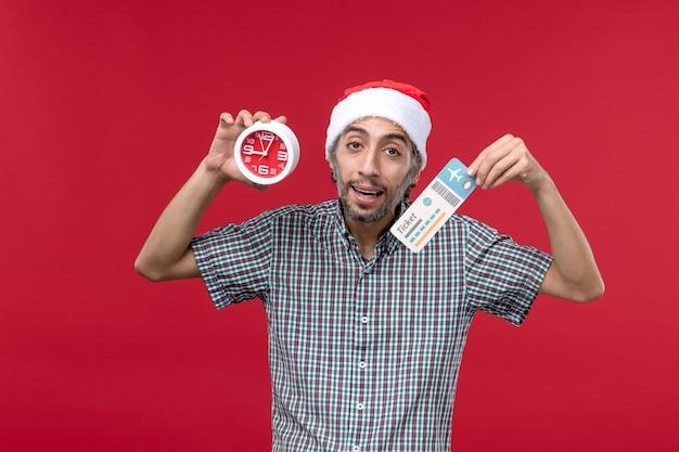 Vue de face jeune homme tenant un billet et une horloge sur fond rouge