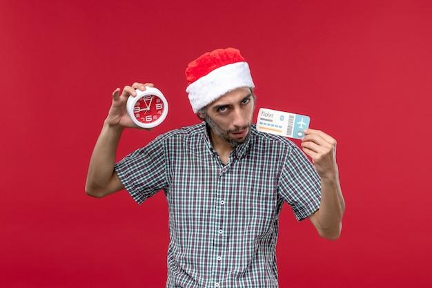 Vue de face jeune homme tenant un billet avec horloge sur fond rouge