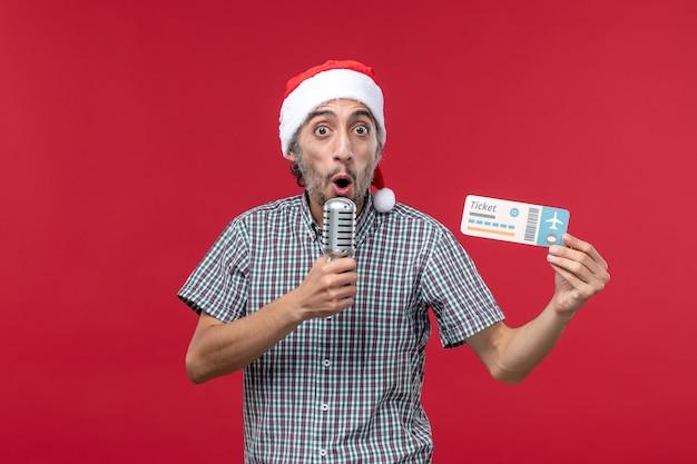 Vue de face jeune homme tenant un billet et un micro sur un bureau rouge