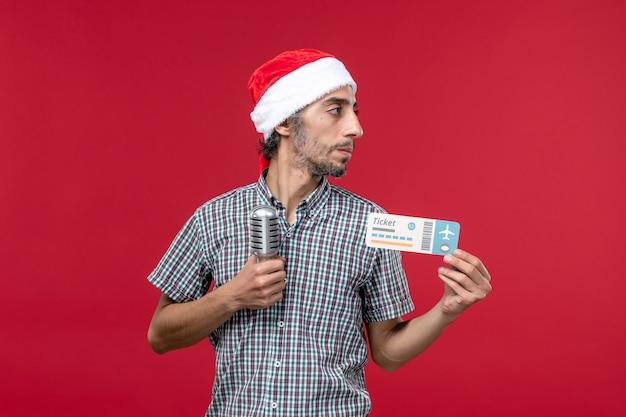 Vue de face jeune homme tenant un billet avec micro sur un bureau rouge