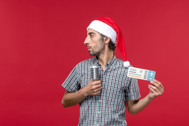 Vue de face jeune homme tenant un billet avec micro sur l'émotion de vacances de musique de plancher rouge