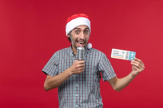 Vue de face jeune homme tenant un billet et un micro sur le fond rouge