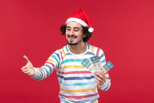 Vue de face jeune homme tenant des billets d'avion sur un bureau rouge avion de nouvel an vacances rouge