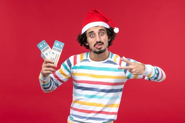 Vue de face jeune homme tenant des billets d'avion sur fond rouge avion vacances nouvel an rouge