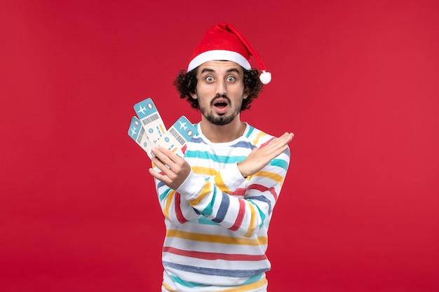 Vue de face jeune homme tenant des billets d'avion sur un fond rouge avion de vacances rouge nouvel an