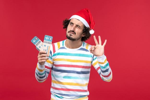 Vue de face jeune homme tenant des billets d'avion sur fond rouge vacances avion nouvel an