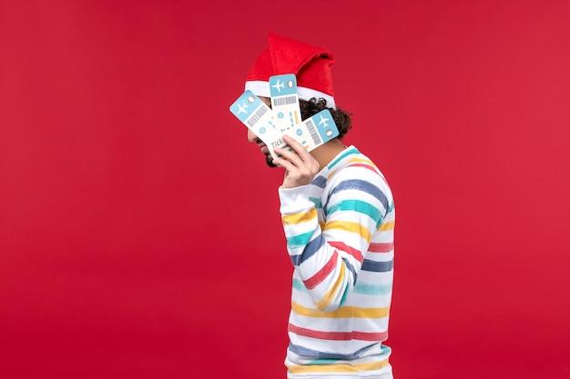 Vue de face jeune homme tenant des billets d'avion sur fond rouge vol avion nouvel an rouge