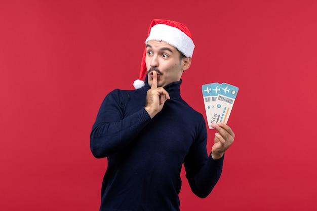 Vue de face jeune homme tenant des billets d'avion sur le fond rouge