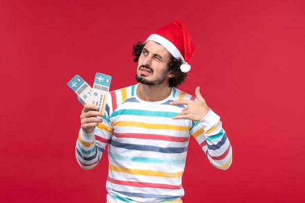 Vue de face jeune homme tenant des billets d'avion sur le mur rouge avion de nouvel an vacances rouge