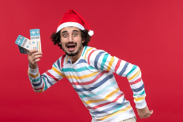 Vue de face jeune homme tenant des billets d'avion sur le mur rouge avion vacances nouvel an rouge