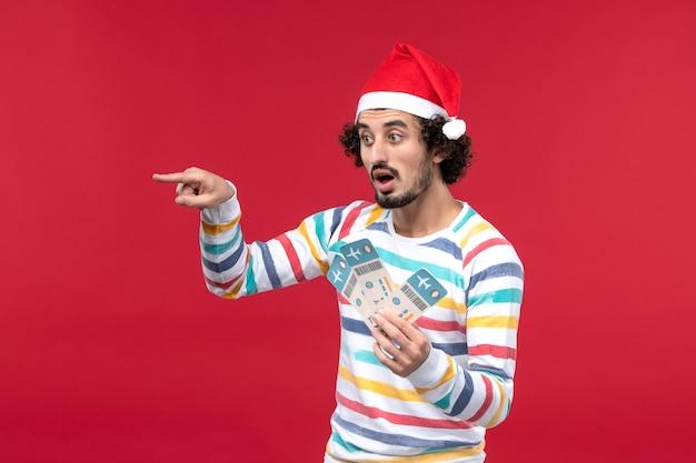 Vue de face jeune homme tenant des billets d'avion sur le mur rouge avion de vacances rouge nouvel an
