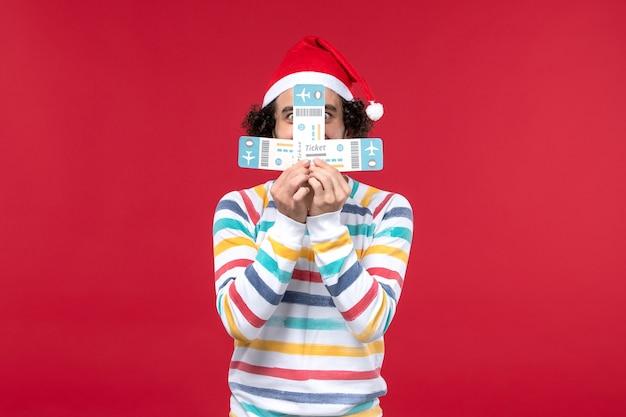 Vue de face jeune homme tenant des billets d'avion sur le mur rouge avion vol nouvel an rouge