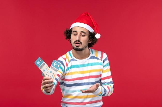 Vue de face jeune homme tenant des billets d'avion sur le mur rouge vacances avion de nouvel an rouge
