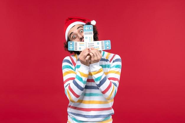 Vue de face jeune homme tenant des billets d'avion sur les vols d'avion de mur rouge nouvel an rouge