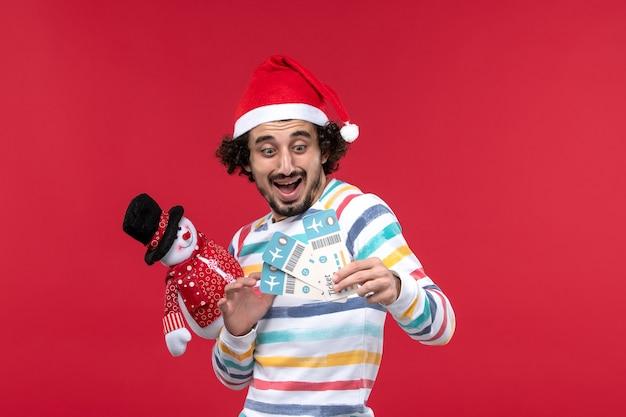 Vue de face jeune homme tenant des billets et des jouets sur le mur rouge mâle vacances rouge nouvel an