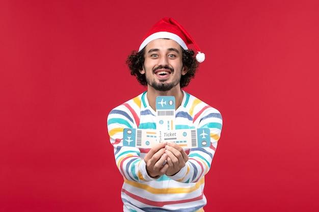 Vue de face jeune homme tenant des billets sur le mur rouge avion vol nouvel an émotion rouge