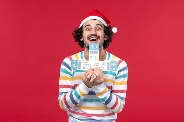 Vue de face jeune homme tenant des billets sur le mur rouge avion vol nouvel an rouge