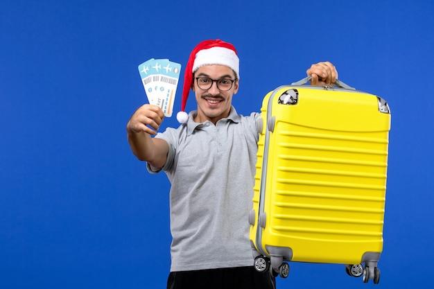 Vue de face jeune homme tenant des billets et un sac lourd sur l'avion de vacances vol fond bleu