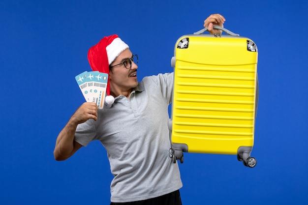 Vue de face jeune homme tenant des billets et un sac lourd sur les avions de vacances vol fond bleu