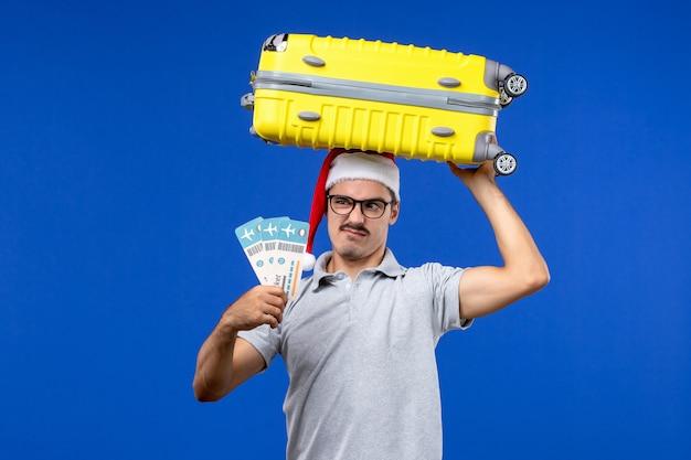 Vue de face jeune homme tenant des billets et un sac lourd sur les avions de vacances de vols de fond bleu