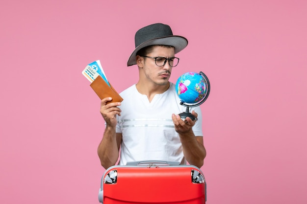 Vue de face d'un jeune homme tenant des billets de vacances et un petit globe sur le mur rose