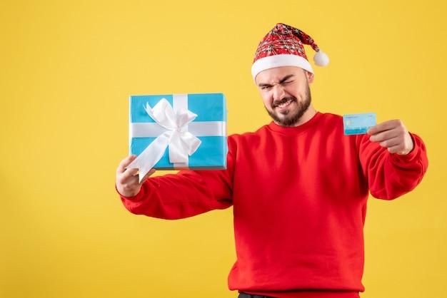 Vue de face jeune homme tenant cadeau de noël et carte bancaire sur fond jaune