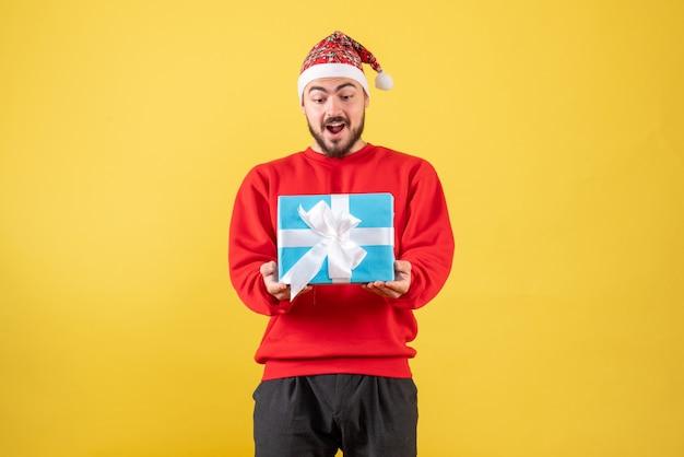 Vue de face jeune homme tenant un cadeau de noël sur fond jaune