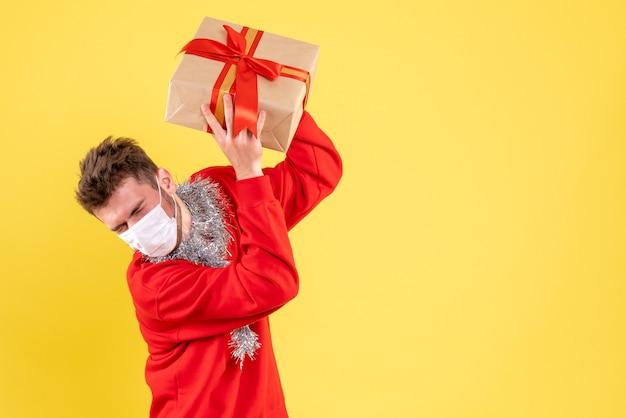 Vue de face jeune homme tenant le cadeau de noël