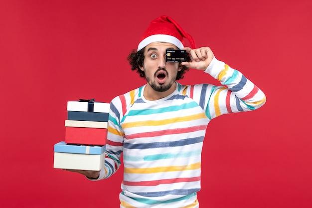 Vue de face jeune homme tenant des cadeaux et une carte bancaire sur le bureau rouge nouvel an argent rouge