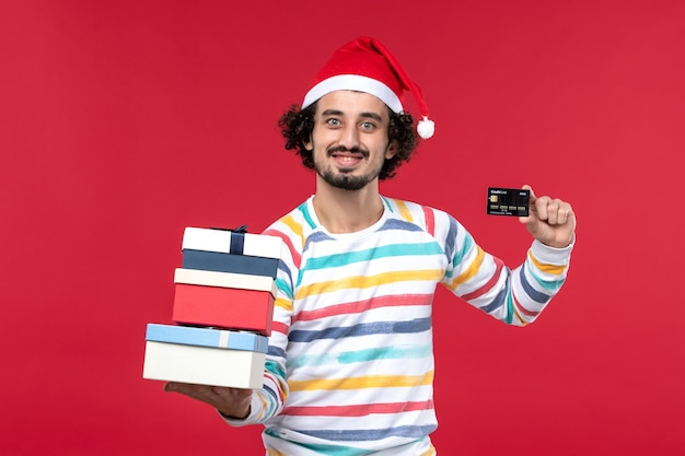 Vue de face jeune homme tenant des cadeaux et une carte bancaire sur le mur rouge nouvel an argent rouge