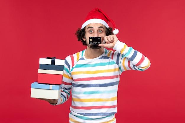 Vue de face jeune homme tenant des cadeaux et carte bancaire sur plancher rouge nouvel an argent rouge