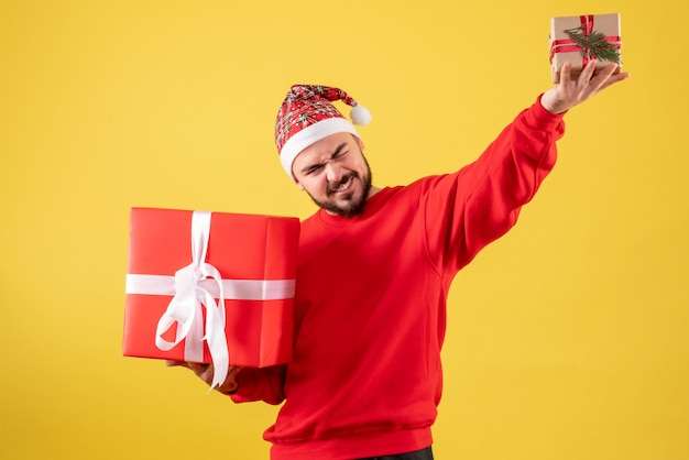 Vue de face jeune homme tenant des cadeaux de noël sur fond jaune
