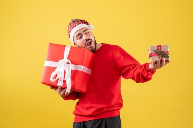 Vue de face jeune homme tenant des cadeaux de noël sur jaune