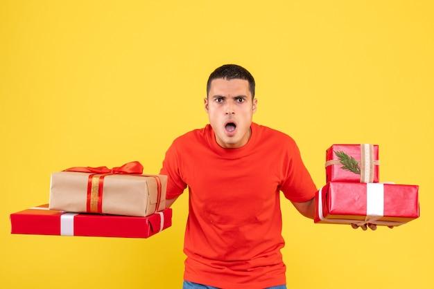 Vue de face jeune homme tenant des cadeaux de noël surpris sur fond jaune