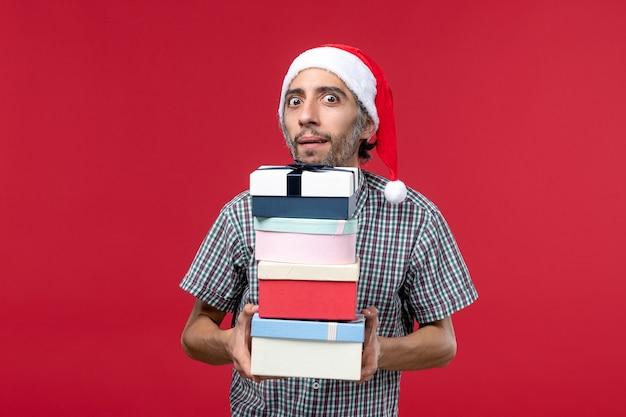 Vue de face jeune homme tenant des cadeaux de nouvel an sur le fond rouge
