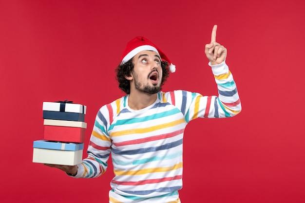 Vue de face jeune homme tenant des cadeaux de vacances sur le mur rouge des émotions du nouvel an rouge