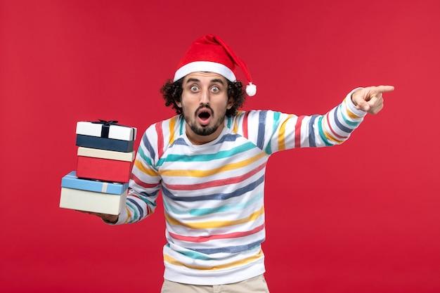 Vue de face jeune homme tenant des cadeaux de vacances sur le mur rouge nouvel an émotion rouge