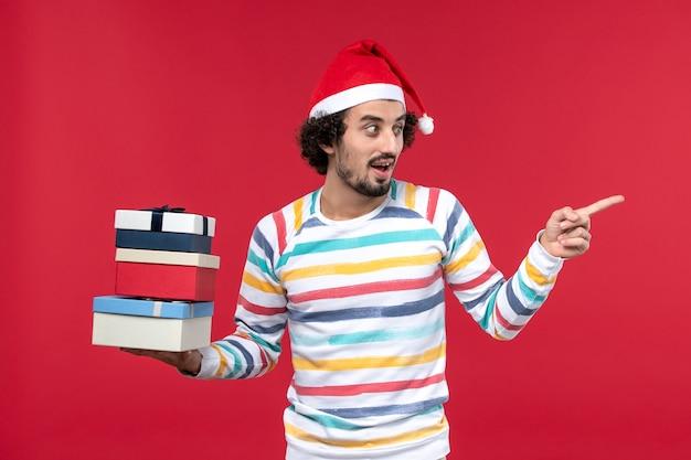 Vue de face jeune homme tenant des cadeaux de vacances sur le mur rouge nouvel an vacances émotion
