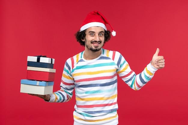 Vue de face jeune homme tenant des cadeaux de vacances sur le mur rouge vacances nouvel an émotions