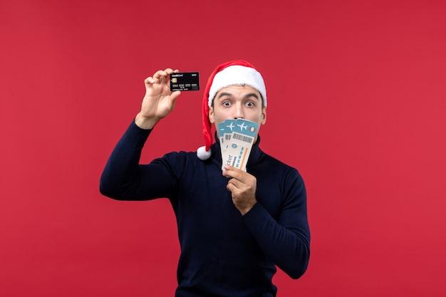 Vue de face jeune homme tenant une carte bancaire et des billets sur fond rouge