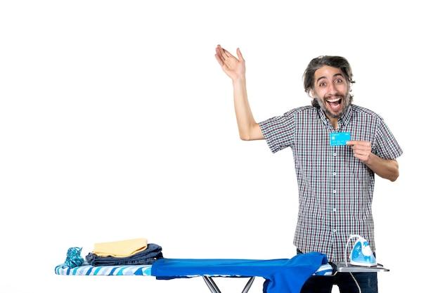 Vue de face jeune homme tenant une carte bancaire derrière une planche à repasser sur fond blanc machine à repasser accueil homme vêtements argent blanchisserie travaux ménagers