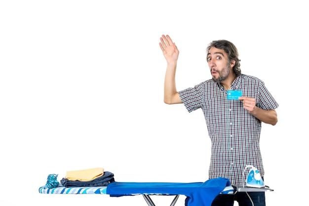 Vue de face jeune homme tenant une carte bancaire derrière une planche à repasser sur fond blanc machine à repasser homme accueil vêtements blanchisserie travaux ménagers argent