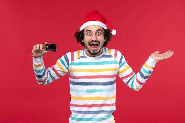 Vue de face jeune homme tenant une carte bancaire sur un mur rouge clair argent émotion mâle rouge vacances
